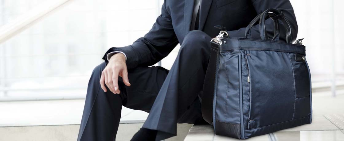 Handsome male business executive sitting on stairs outside a building with his bag